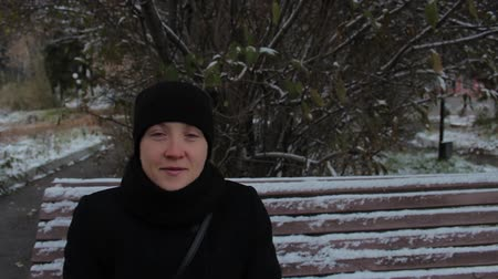 sentiment : Portrait of a smiling girl in a black dress, sitting on a snow-covered bench in the park in winter Stock Footage