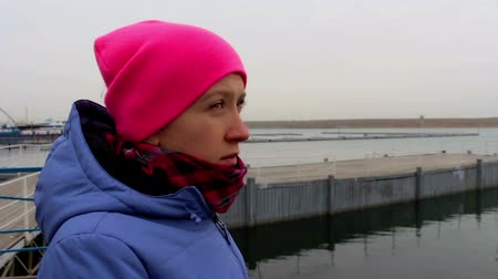 созерцать : Portrait of a girl in a pink hat on the pier on a cold cloudy day in autumn. Young woman looks into the distance Стоковые видеозаписи