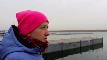 sentiment : Portrait of a smiling girl in a pink hat on the pier on a cold cloudy day in autumn Stock Footage