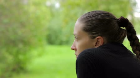 созерцать : Close-up of a pensive girl with a dreamy look on the background of green foliage