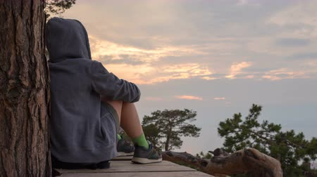 созерцать : Cinemagraph - girl in a hoodie sits, and contemplates the sky. 4k, time lapse