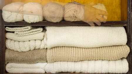 raflar : Hand takes the balls of wool, knitting needles, woolen fabrics from the shelves