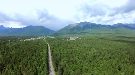 cloud scape : Dramatic aerial view of beautiful mountains, green forest landscape and town. Road to the mountains. Drone flying, aerial camera shot. Siberia. 4k Stock Footage