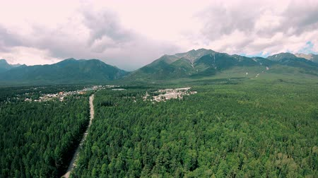 Aerial view of mountains, dark green forest landscape, road and town