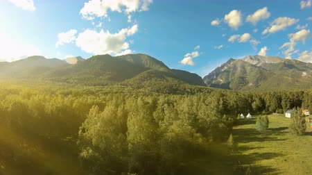 wschód słońca : Aerial shot above the meadow and trees. Flight to the mountains. Drone flies forward over the green field and forest, flying beside a Buddhist temple. Sun flare