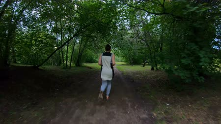 kocogó : Jogging in the park. Girl running along the forest path. Back view. Slow motion