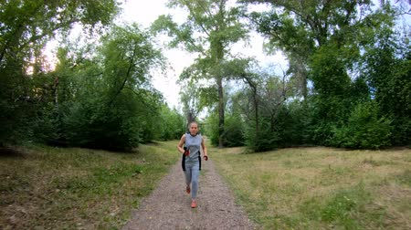 ジョガー : Jogging in the park. Girl running along the forest path. Front view. Slow motion