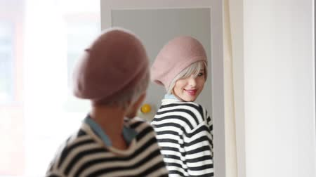kifejező pozitivitás : Young blonde girl in beret dressing up at home near a mirror. Stock mozgókép
