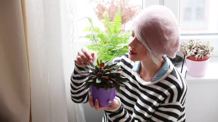 Young girl with plant in a pot near a window