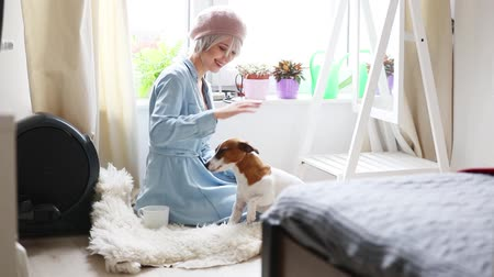 Young blonde girl with dog at home interior