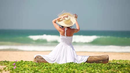 Young girl in hat and white dress sitting on the beach in summerime