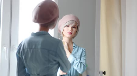 Young blonde girl dressing up at home near a mirror. Stok Video