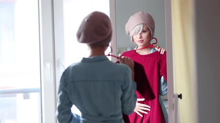Young blonde girl in beret dressing up at home near a mirror. Stok Video