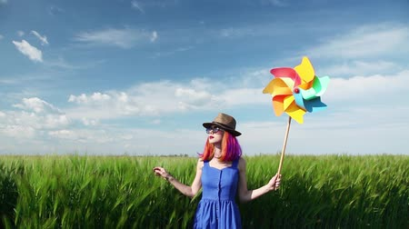 purple hair girl with pinwheel at wheat field