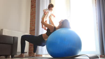 Young mother and child making a physical exercises at home. Stok Video