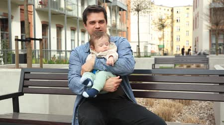 Young father and child sitting on bench on home yard