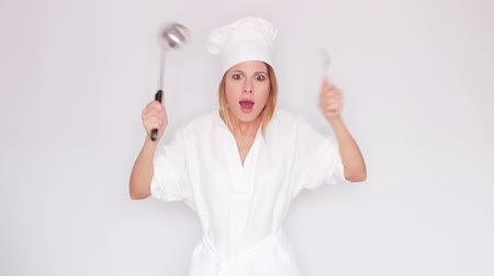 woman in cook uniform talking and holding kitchenware