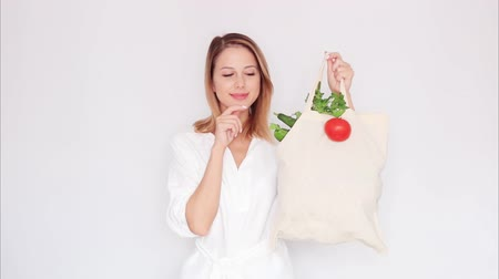 woman in white clothes showing bag with different vegetables
