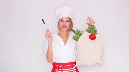 woman in cook uniform holding bag with different vegetables and french flag Stok Video