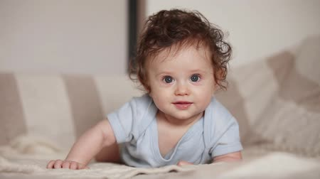 Little child boy with blue eyes in white bed Stok Video