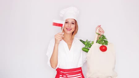 woman in cook uniform holding bag with different vegetables and polish flag Stok Video