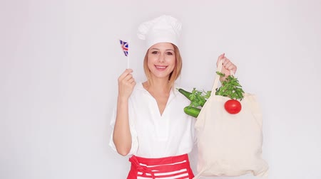 woman in cook uniform holding bag with different vegetables and british flag