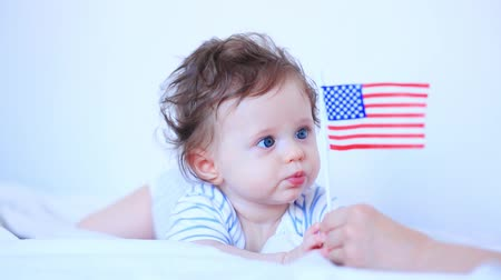Little child boy with blue eyes and american flag in white bed Stok Video