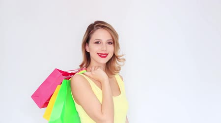 Young redhead girl with shopping bags on white background Stok Video