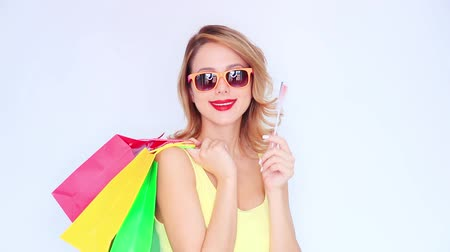 Young redhead girl with shopping bags and french flag on white background Stok Video