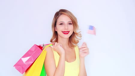 ruj : Young redhead girl with shopping bags and USA flag on white background Stok Video