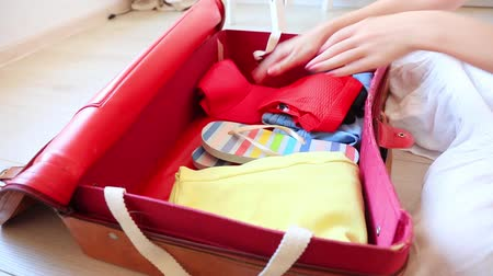 chapéu : Young girl prepearing for vacation. Pack up clothes in suitcase at home.
