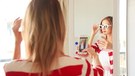 selfie girl : Young girl dressing up near a mirror. Choosing a clothes for vacation and making a selfie