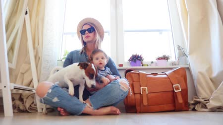 chapéu : Young mother with a child sitting on a floor near dog and suitcase with a window. Person is ready for summertime vacation