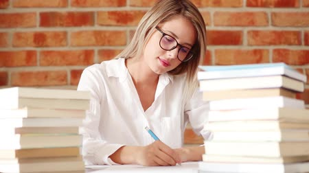 espetáculos : Footage of a woman in glasses sitting at table with books and writing on brick wall background