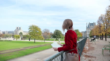 parisli : Style redhead girl in red coat with map looking for something in park in Paris. Autumn season time