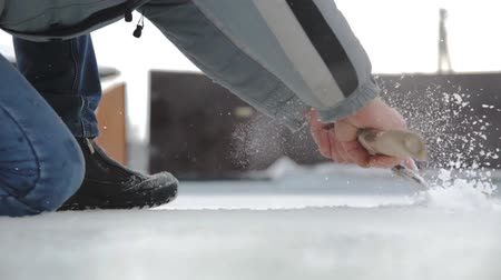 desigual : Man cleans irregularities on the surface of ice