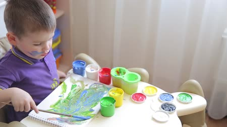 resimlerinde : Beautiful child draws with colored paints while sitting at table Stok Video