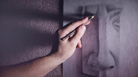 grafit : A man artist paints a plaster sketch of the nose with a graphite pencil Stok Video