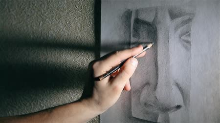 grafit : Man artist draws a nose with a graphite pencil