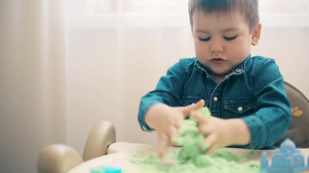 elpusztít : The boy plays with kinetic sand and develops motor skills of hands