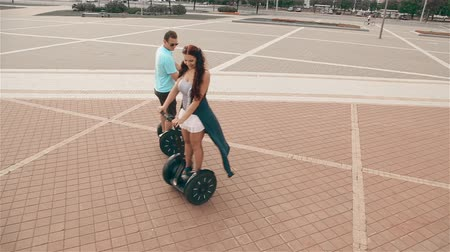 balanceamento : Loving couple rides a hoverboard on the road in the city