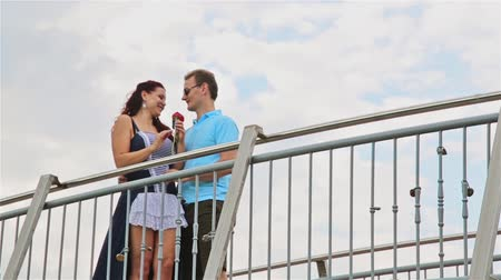 presented : The man on the bridge surprised the beautiful girl, giving her a flower, a red rose