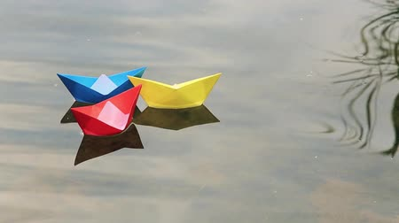 sea breeze : Three small colored paper boats floating on the water Stock Footage