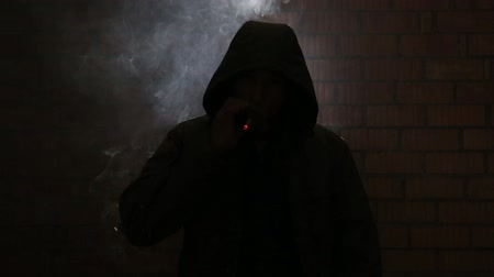 bad habits : Maniac smokes nervously waiting for his victim in a dark alley Stock Footage