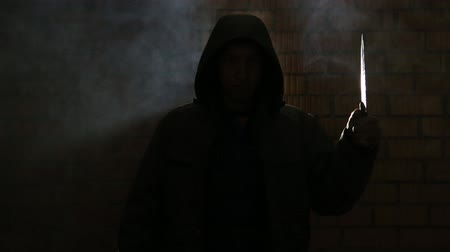 serial : A man with a knife in a dark smoky room
