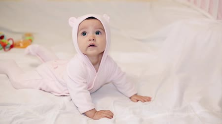 salya : A little girl in a pink bear costume lying on a white blanket Stok Video