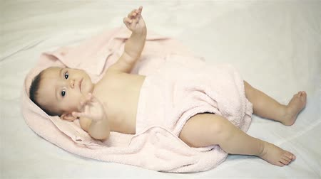 fürdés : Little girl lying in a towel on a white blanket after bathing Stock mozgókép