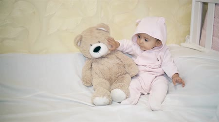 плюшевый мишка : A little girl in a bear costume sitting next to a Teddy bear