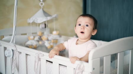kreş : A little girl standing in a crib watching someone carefully 1080p HD