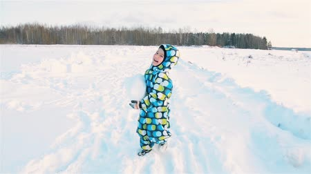 comes : A boy in a colored jumpsuit smiling carries a big snowball Stock Footage